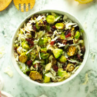 white bowl of Brussels sprouts salad with cranberries and almonds