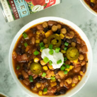 A bowl of vegan 3-bean chili topped with pickled jalapenos, vegan sour cream, and chopped green onion