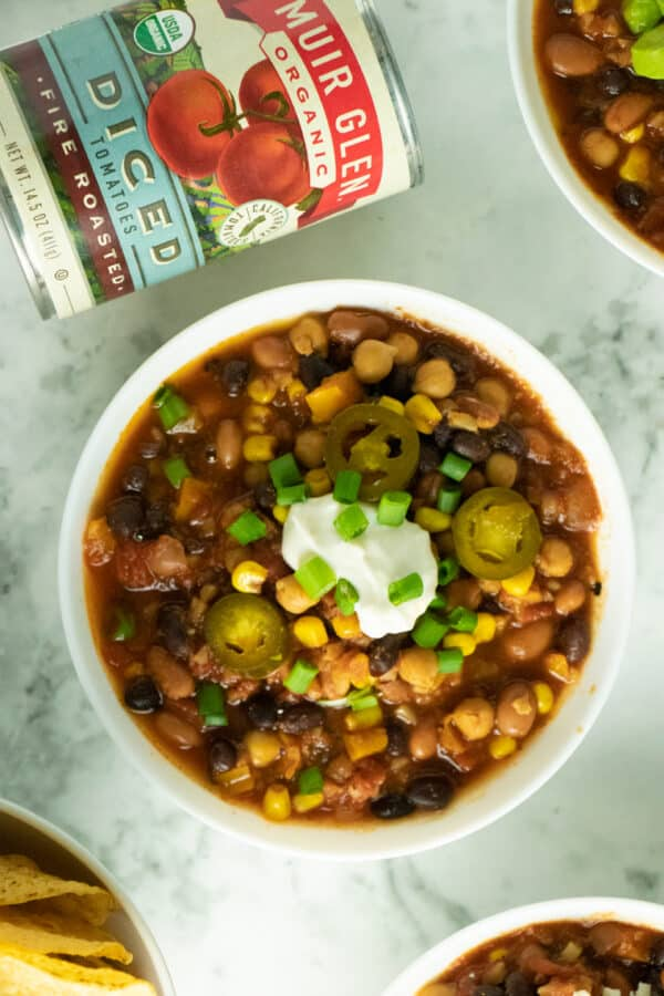 overhead photo of vegan 3-bean chili in a white bowl with vegan sour cream, pickled jalapenos, and green onion next to a can of Muir Glen tomatoes