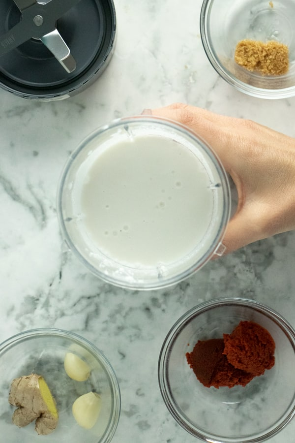 hand placing coconut milk in a blender canister onto the table