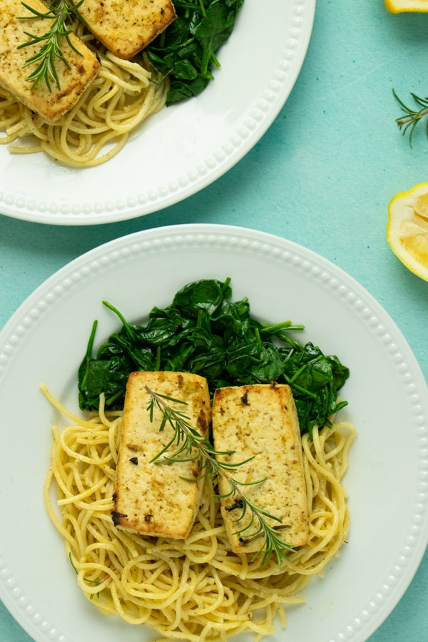 overhead photo of lemon herb tofu on plates with spaghetti and spinach and fresh rosemary on top as the garnish