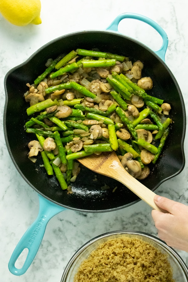 hand stirring sauteed mushrooms and asparagus in a cast iron skillet