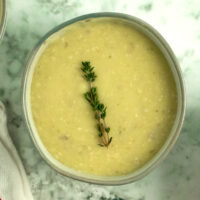 bowl of potato leek soup on a marble tabletop with a piece of fresh thyme as garnish