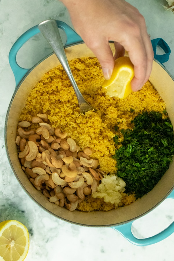 hand squeezing lemon into a pot of couscous with basil, garlic, and cashews