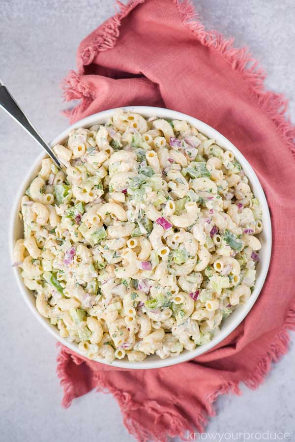 big white bowl of vegan pasta salad with creamy sauce and red onions