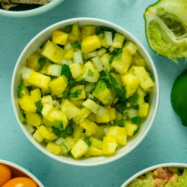 bowl of pineapple salsa on a table next to a juiced lime and bowls of orange tomatoes, guacamole, and chips