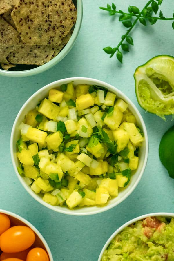 white bowl of pineapple salsa next to bowls of chips, guac, and yellow tomatoes
