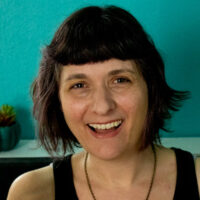 photo of a smiling woman with short hair sitting in front of a teal wall