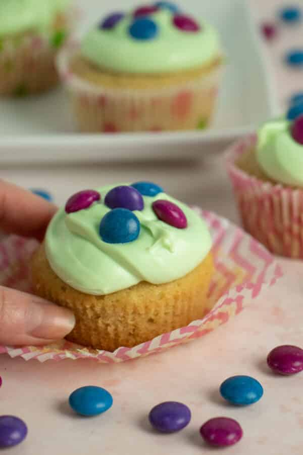 hand picking up a vegan Easter cupcake with green frosting and chocolate candy on top