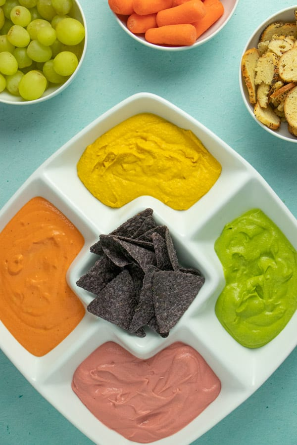 white serving tray with 5 sections full of colored hummus and blue corn chips. Bowls of other snacks on the table