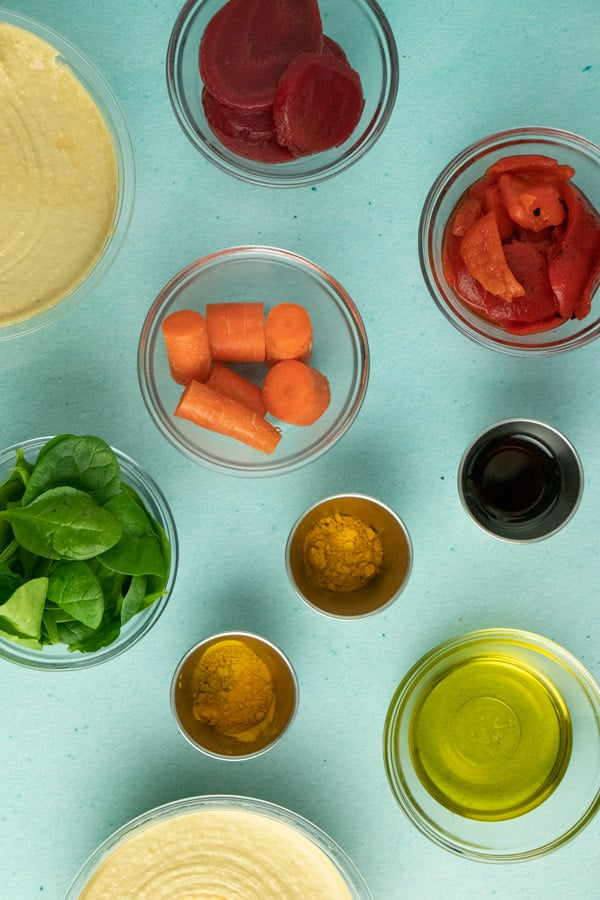 mise en scene of rainbow hummus ingredients in glass and metal bowls on a blue table
