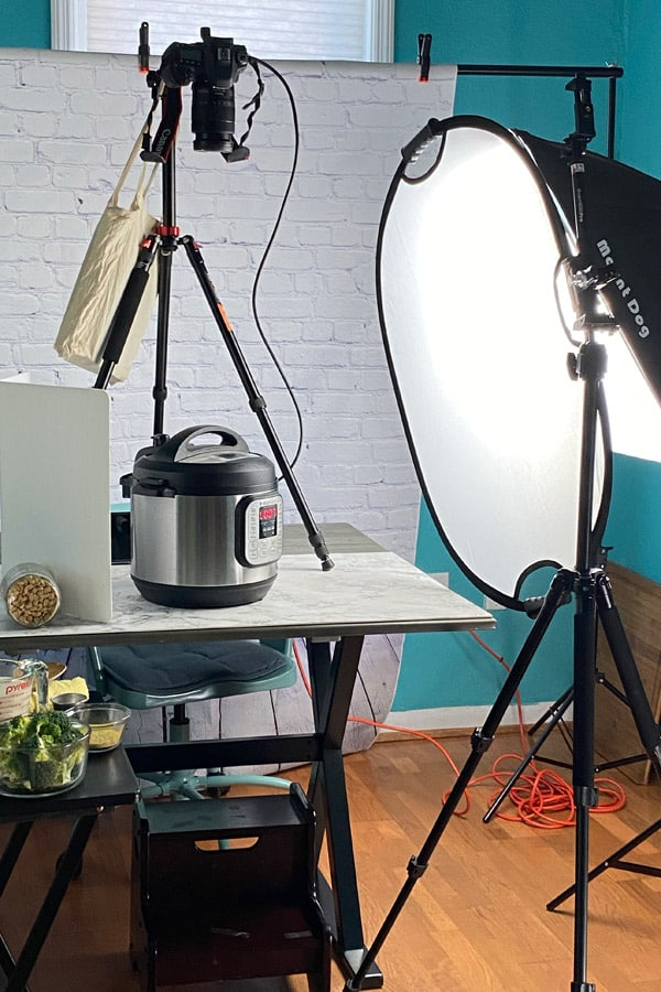 picture of an overhead shooting setup of an Instant Pot on a table with a light, two tripods, and an overhead camera