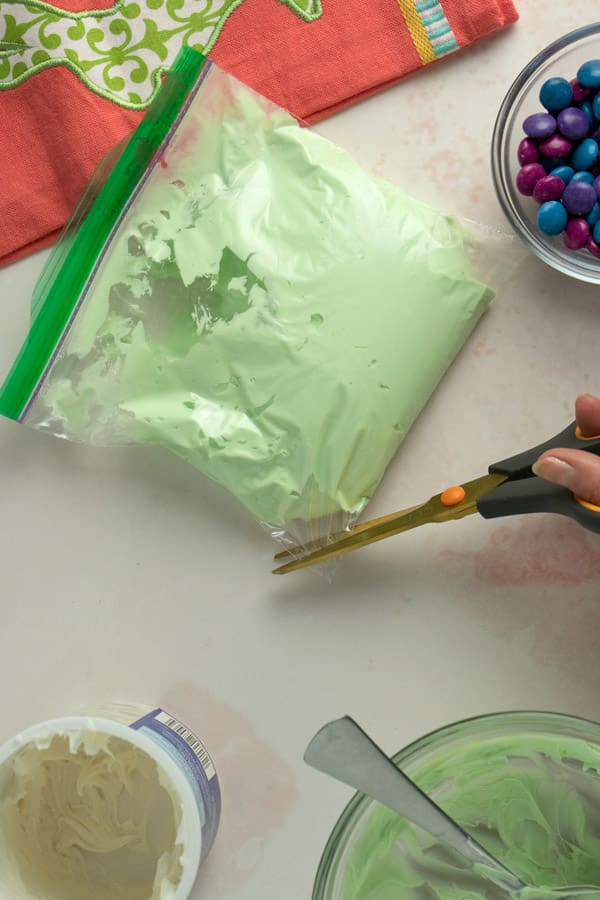 hand using scissors to snip the corner off of a plastic baggie to make a DIY piping bag