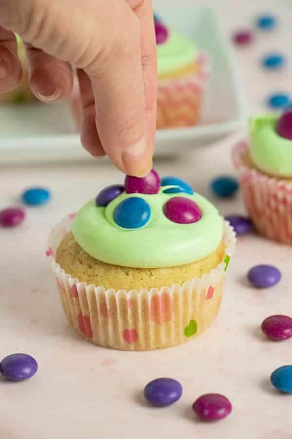 "adding the candy ""eggs"" to the top of a frosted vegan Easter cupcake"