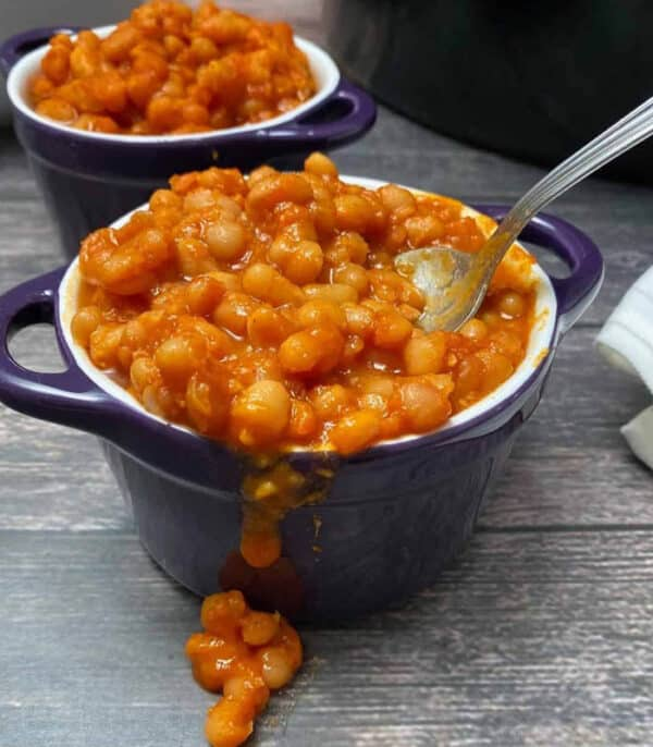 two deep purple bowls of vegan baked beans on a gray table next to a slow cooker