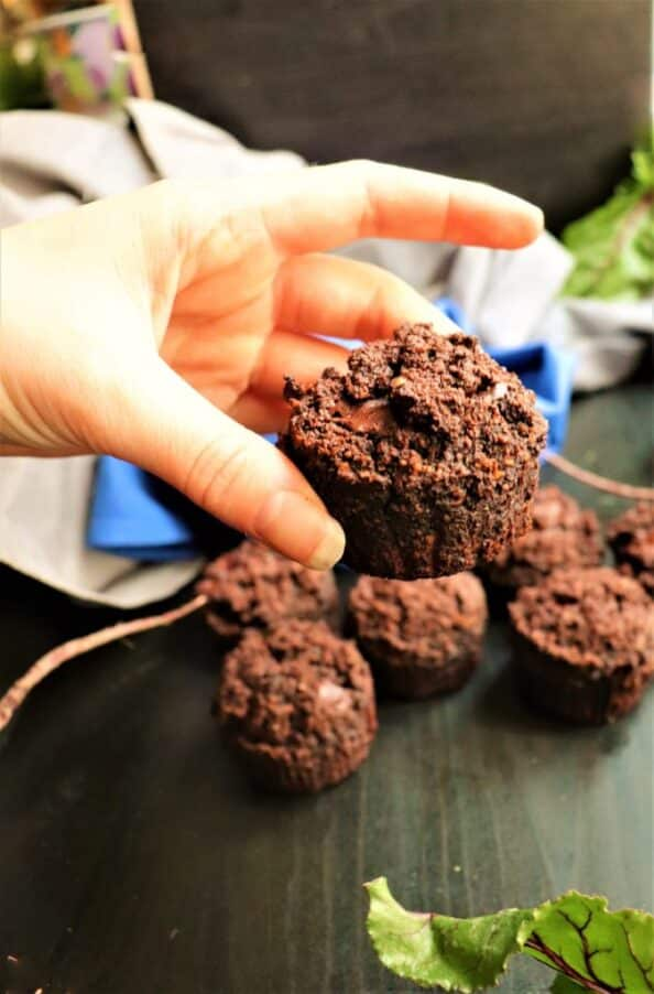 hand lifting a vegan chocolate muffin off of a table with more muffins on it