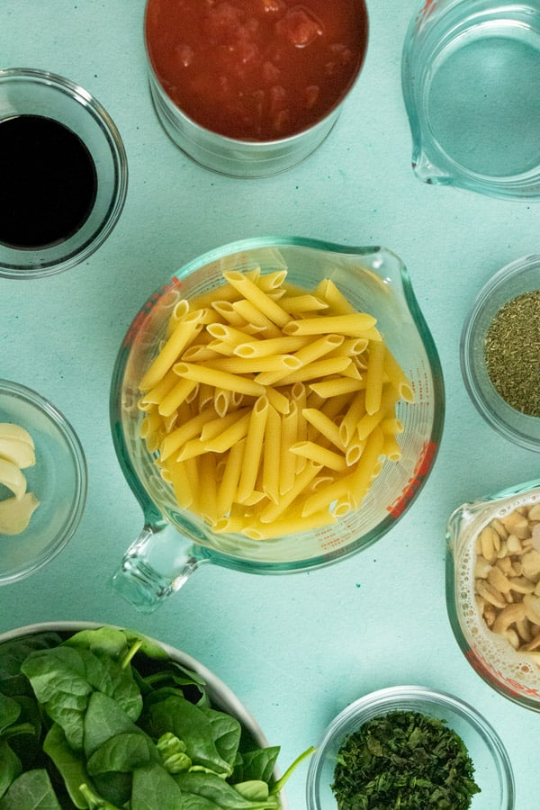 overhead photo of bowls of penne, spinach, soaking cashews, canned tomatoes, balsamic vinegar, and herbs and spices on a blue table