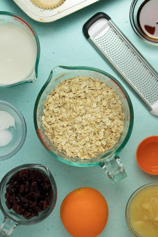 measuring bowl of oatmeal surrounded by bowls of dried cranberries, applesauce, baking powder, oat milk, maple syrup, an orange, and a citrus zester