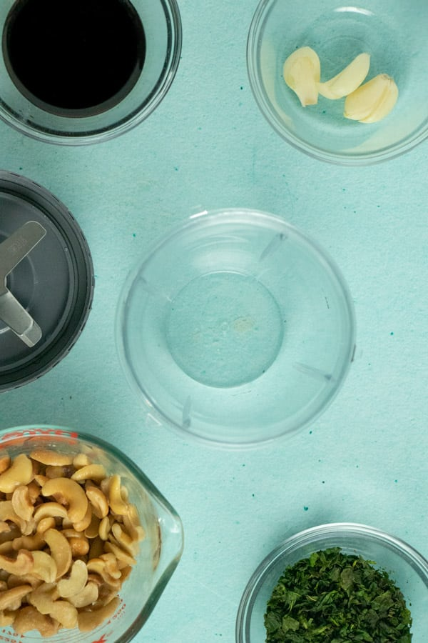 blender canister on a table next to the blade with bowls of soaked cashews, minced basil, garlic cloves, and balsamic vinegar