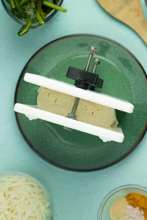 overhead photo of pressing tofu in a tofu press on a green plate with spinach, cheese, and spices on the table