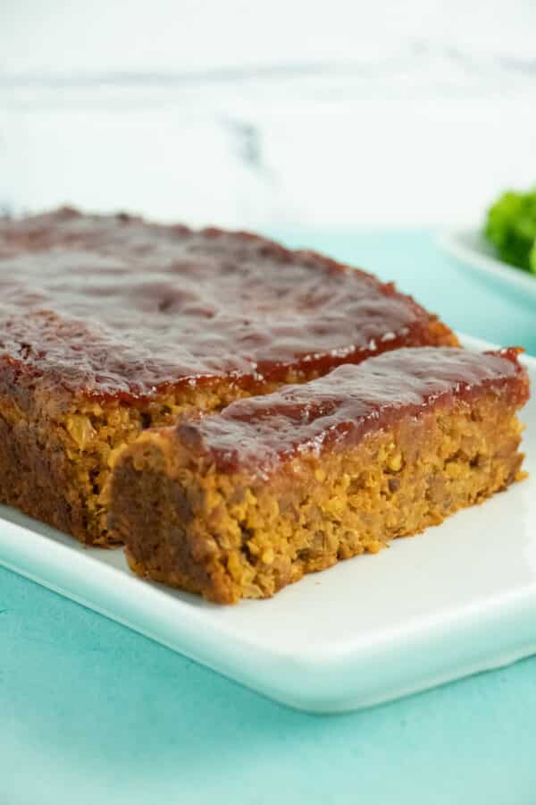 A close up of a sliced vegan meatloaf on a white serving tray