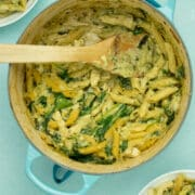 A Dutch oven with Pasta and spinach in a creamy sauce