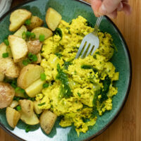 A plate of tofu scramble with a side of breakfast potatoes sitting on top of a wooden table