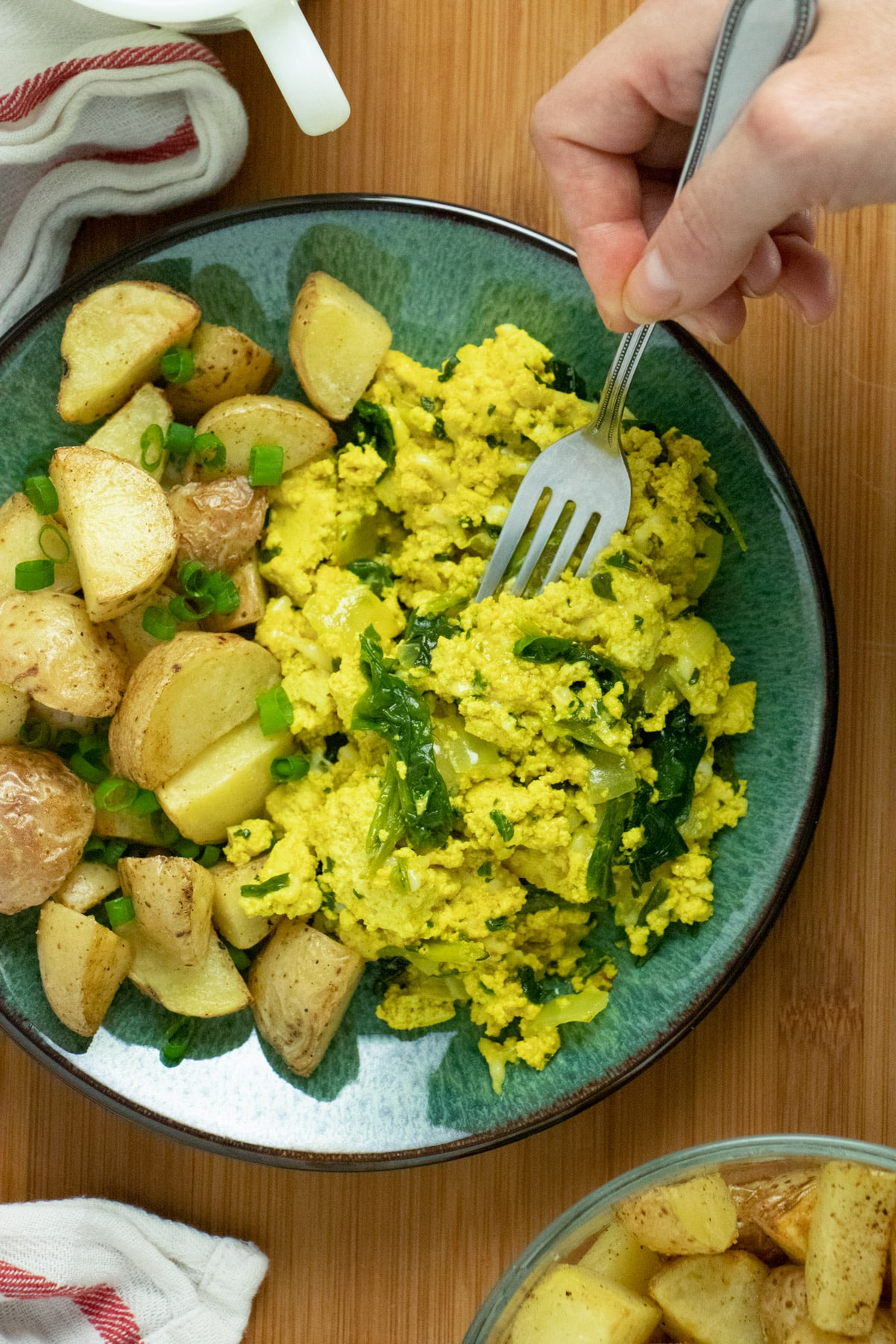 a turquoise plate of tofu scramble and potatoes with a fork taking a bite of the scramble