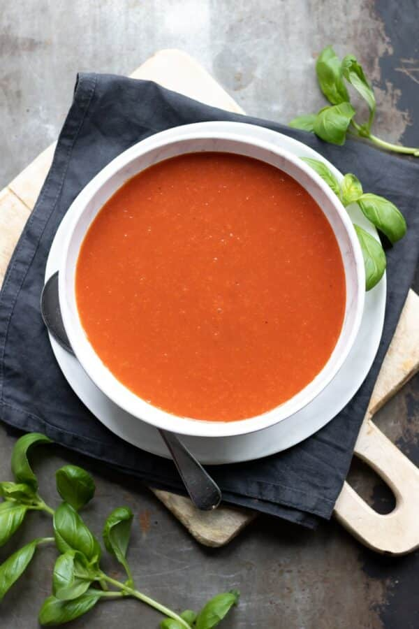 white bowl of tomato soup on a black napkin on a gray tabletop with fresh basil around it