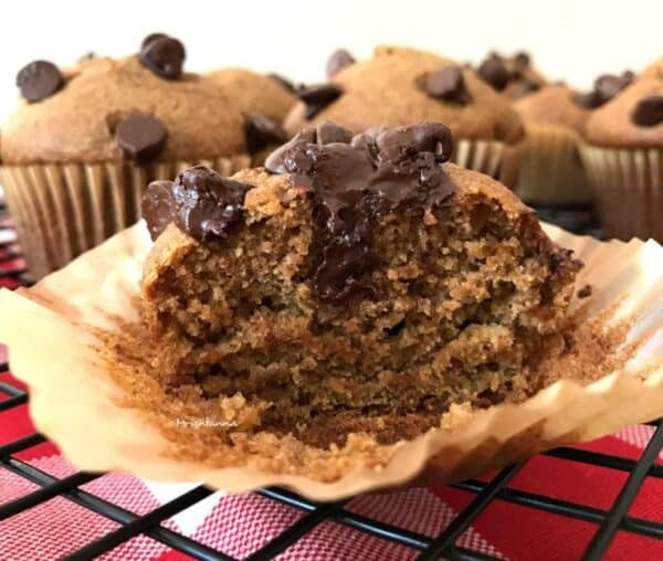 close-up of a vegan chocolate chip almond butter muffin cut in half, so you can see the moist insides