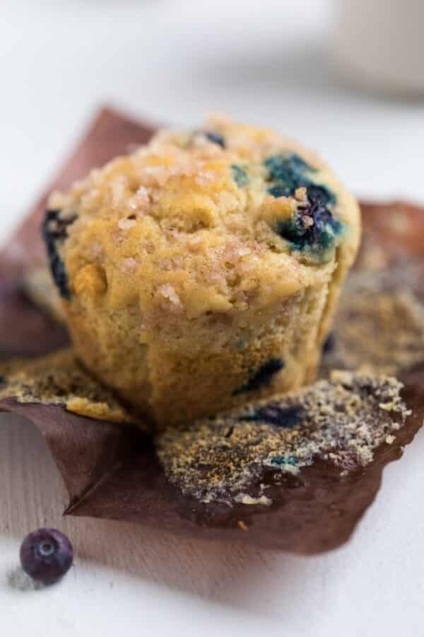 close-up of a vegan blueberry muffin unwrapped from the pan liner
