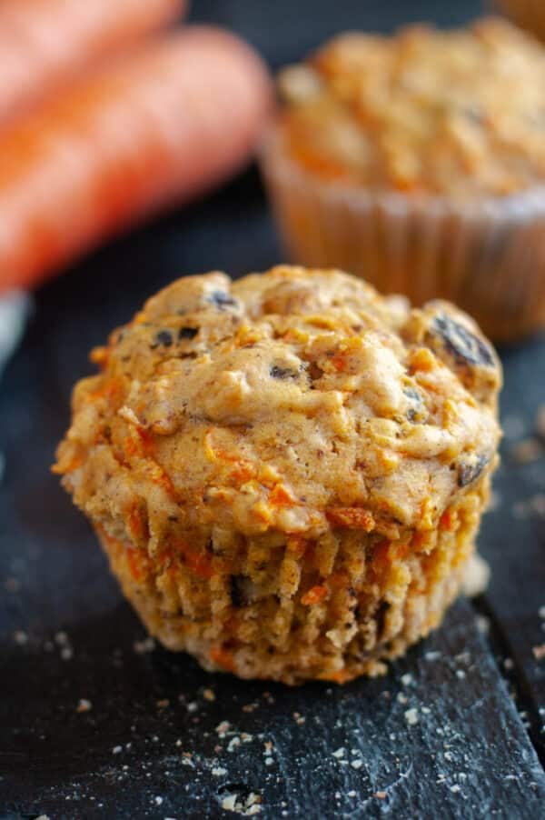 close-up of a vegan carrot raisin muffin with carrots and another muffin in the background