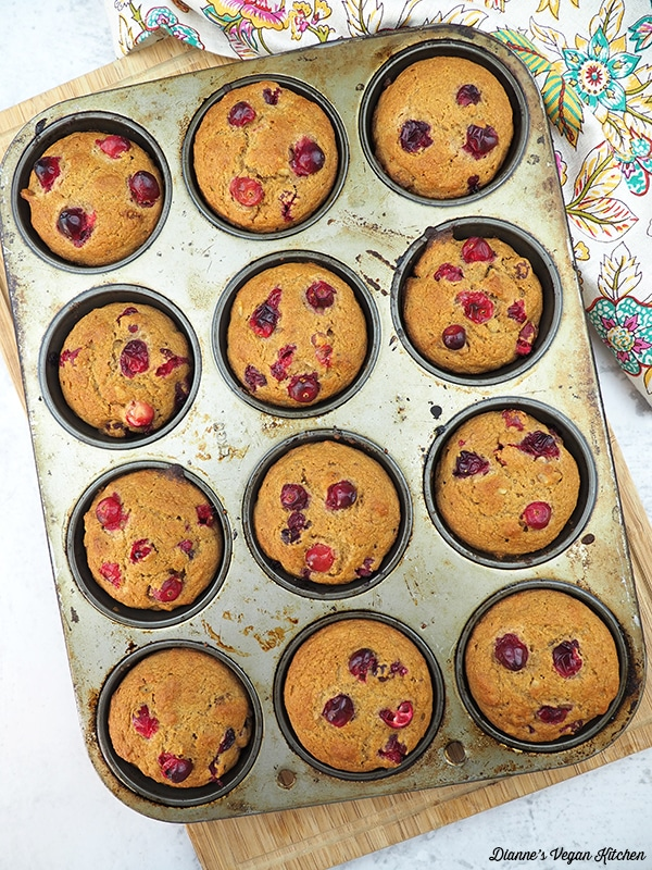 overhead photo of a muffin pan full of vegan orange cranberry muffins