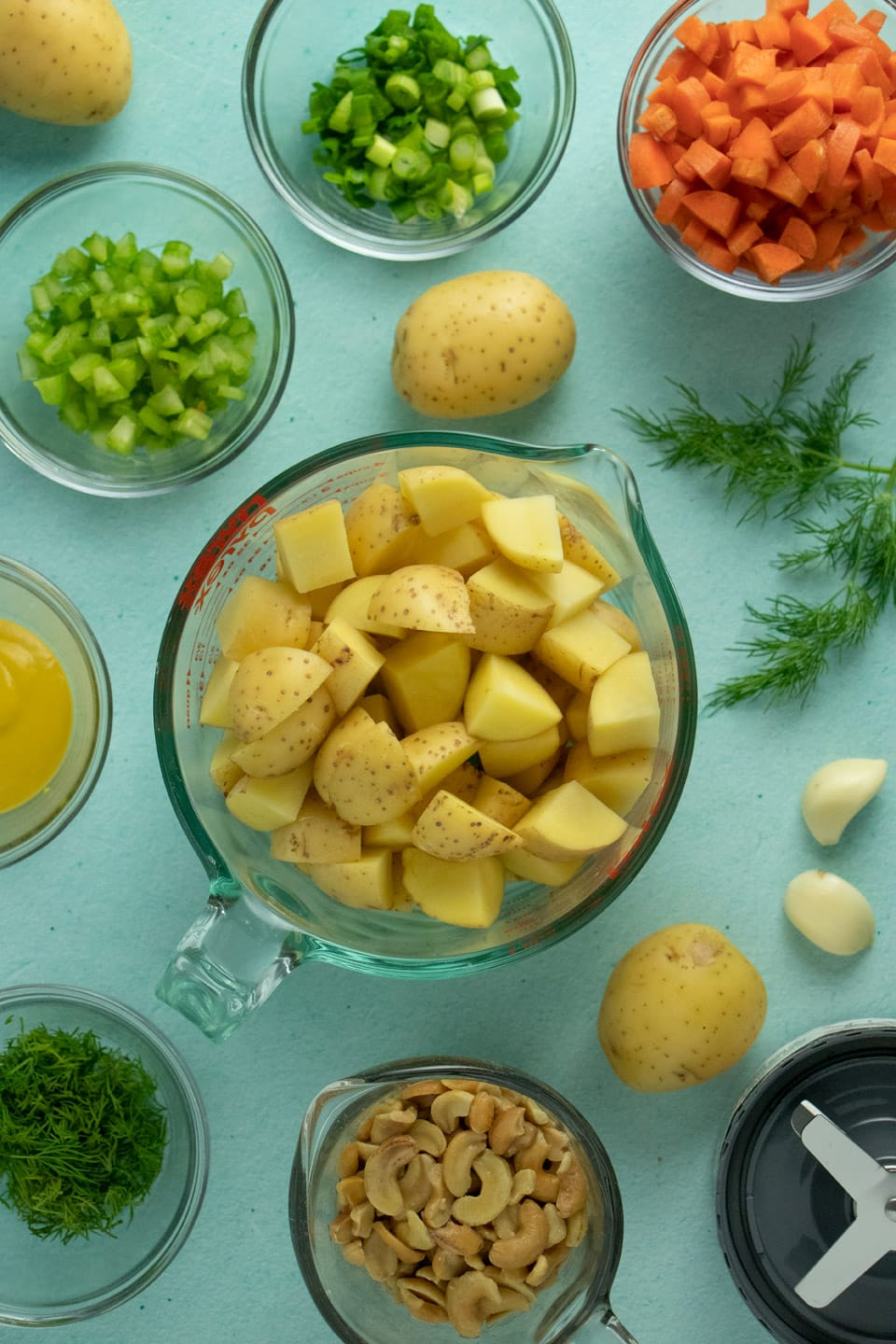 blue table with glass bowls of cubed potatoes, diced vegetables, garlic cloves, whole potatoes, soaked cashews, and a blender blade