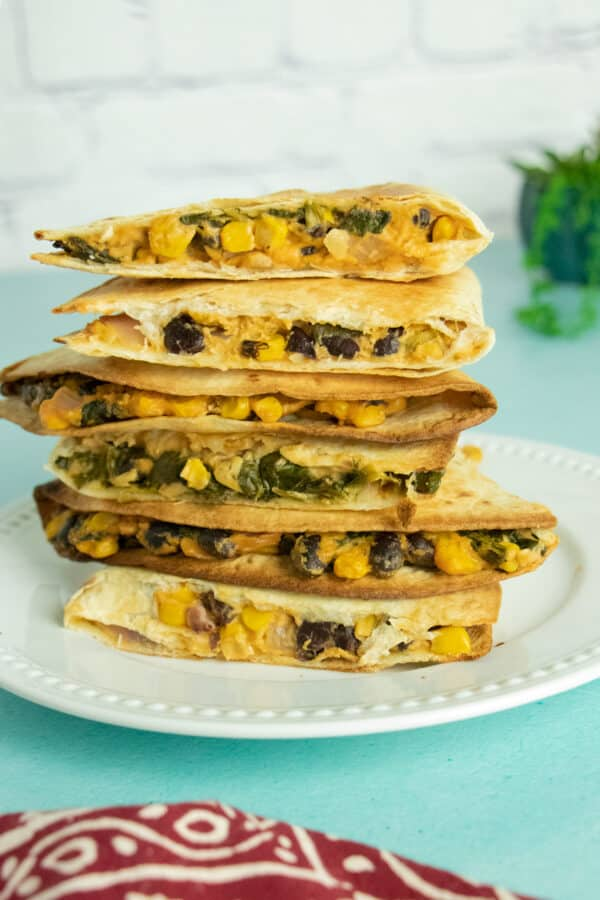 photo of a white plate on a blue table, piled high with pieces of vegan quesadilla. You can see the spinach, roasted corn, and black beans in the filling.