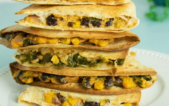 a stack of vegan quesadillas with beans and corn on a white plate