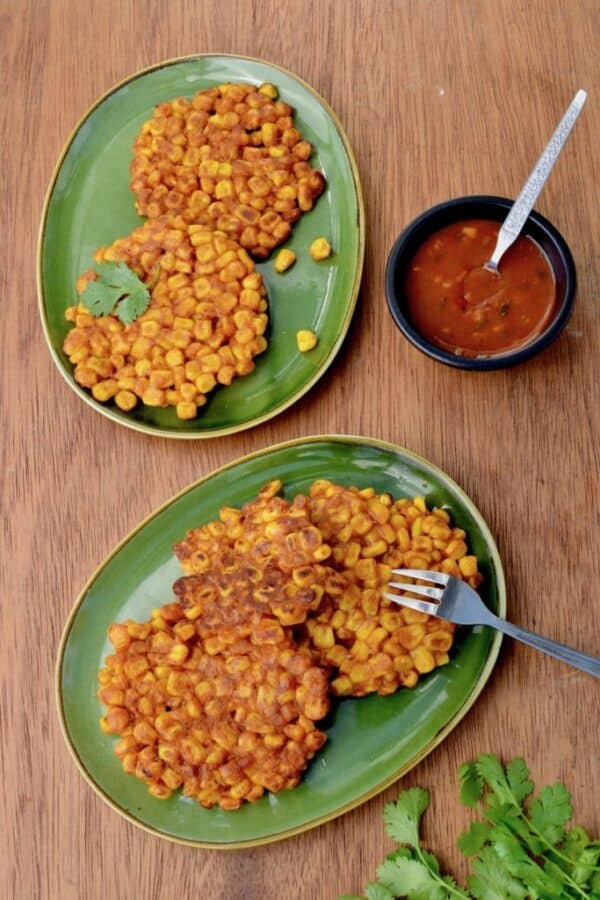 wooden table with two green plates of sweetcorn fritters next to a small serving bowl of salsa