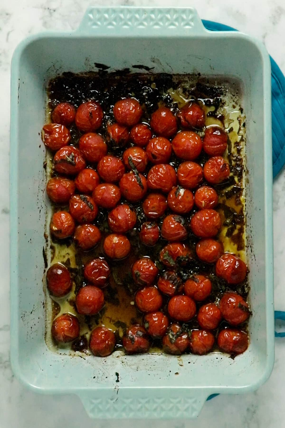 overhead photo of roasted cherry tomatoes in a light blue baking pan