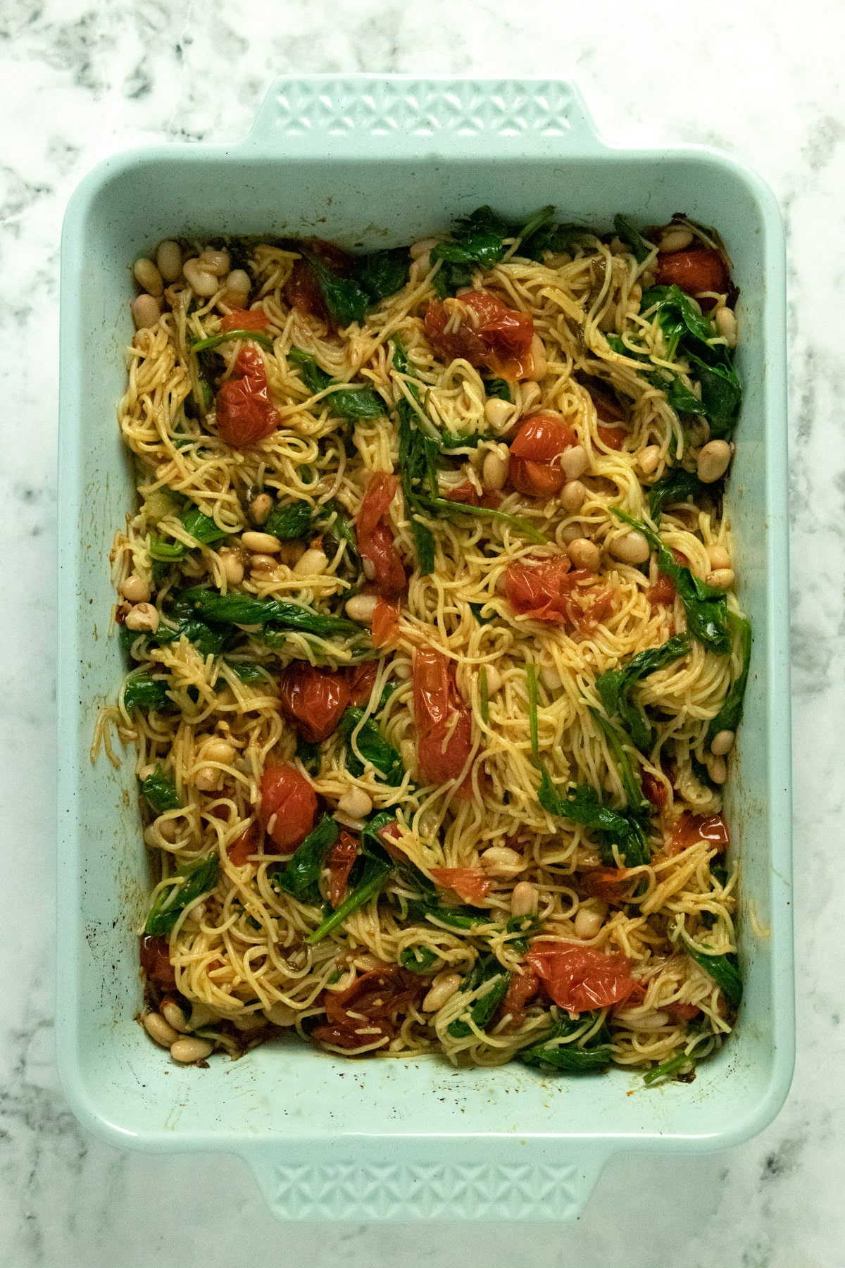 overhead photo of roasted cherry tomato pasta with basil, garlic, spinach, and beans in a blue baking pan