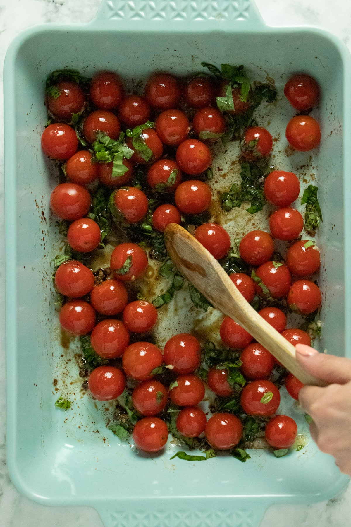 overhead photo of wooden spoon stirring cherry tomatoes with olive oil, vinegar, garlic, and basil in a light blue baking pan