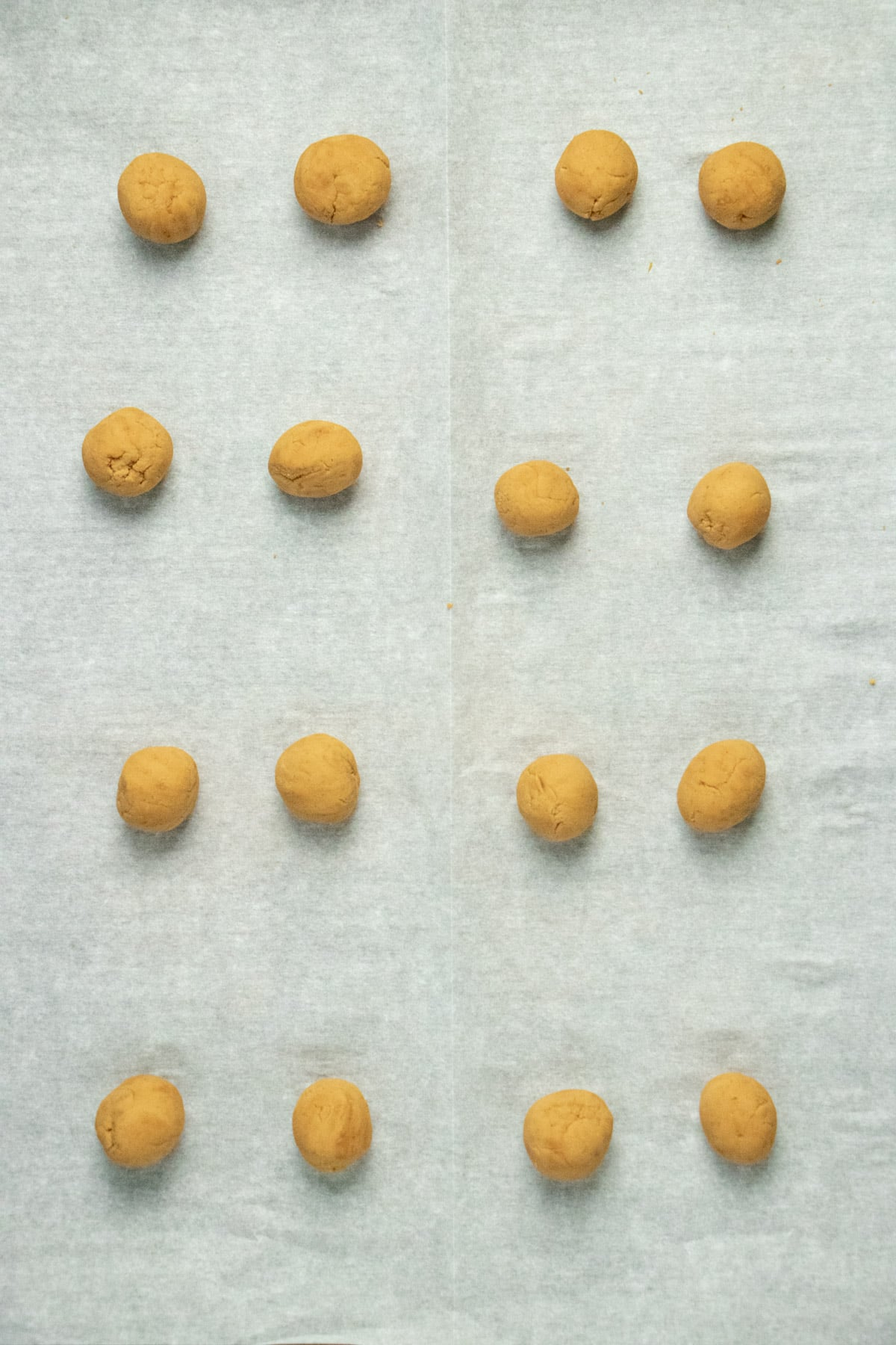 chilled balls of peanut butter dough on a piece of white parchment paper