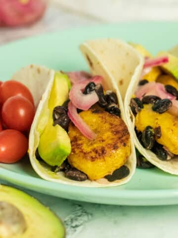 close-up of plantain tacos with red onion, black beans, and sliced avocado. Grape tomatoes on the side