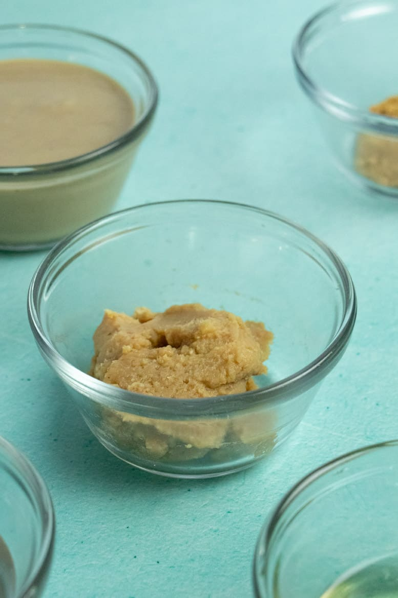 small bowl of white miso on a blue table surrounded by bowls of tahini, ground ginger, water, and rice vinegar