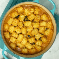 overhead photo of vegan tater tot casserole in a Dutch oven