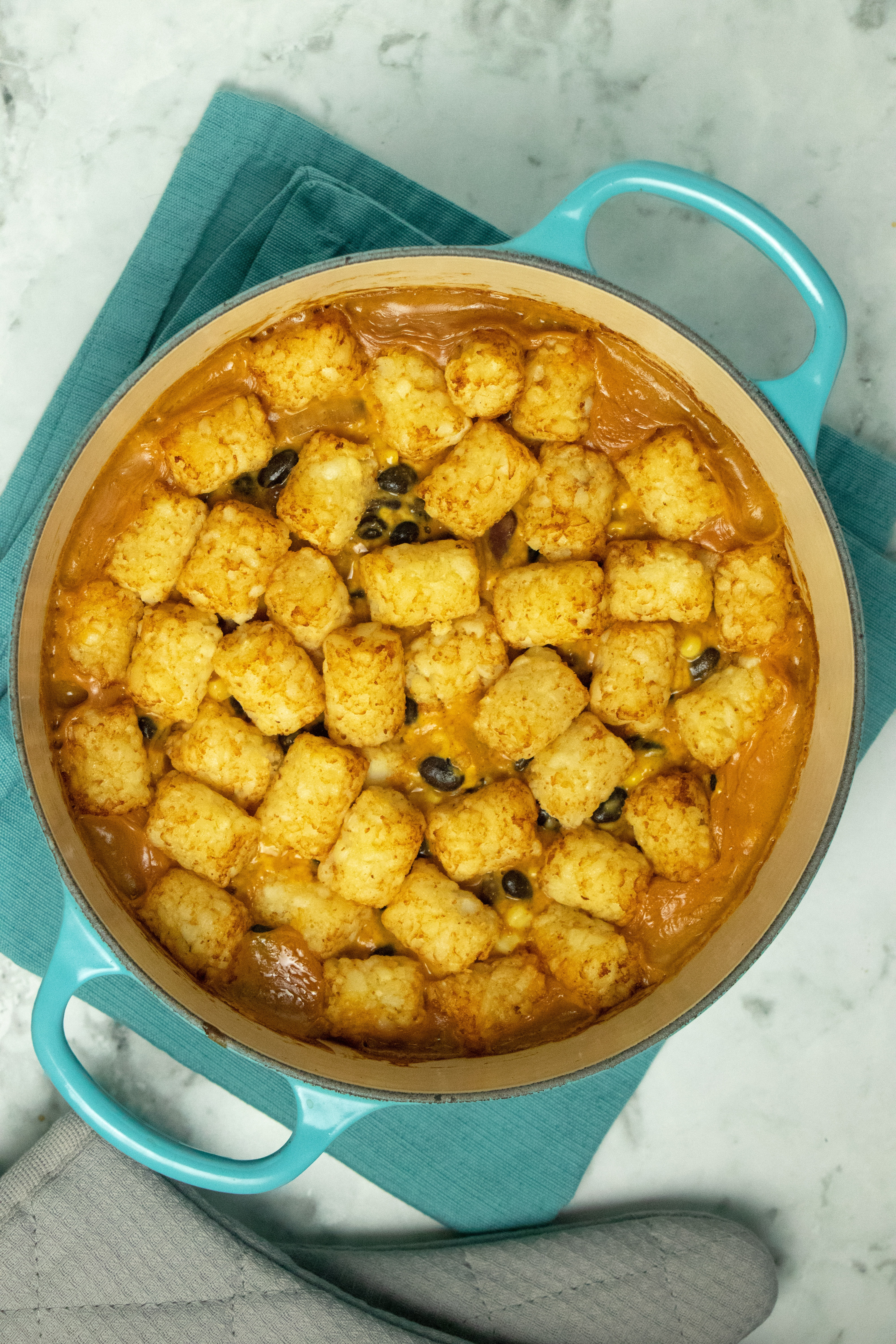 cheesy chili vegan tater tot casserole in a blue Dutch oven, after baking. The tots are browned, and you can see the cheese sauce bubbling up