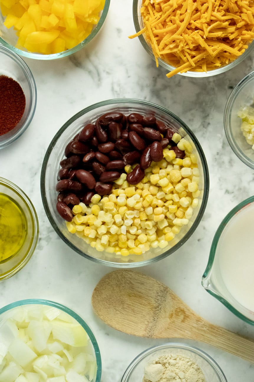 a wooden spoon and glass bowls on a marble countertop that are holding beans, corn, vegan milk, chopped vegetables, olive oil, and chili powder