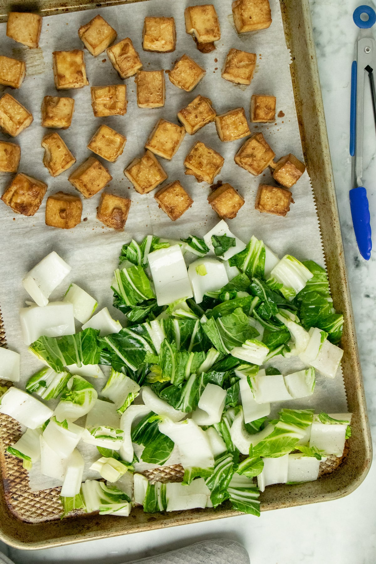 adding bok choy to a baking sheet of baked crispy tofu