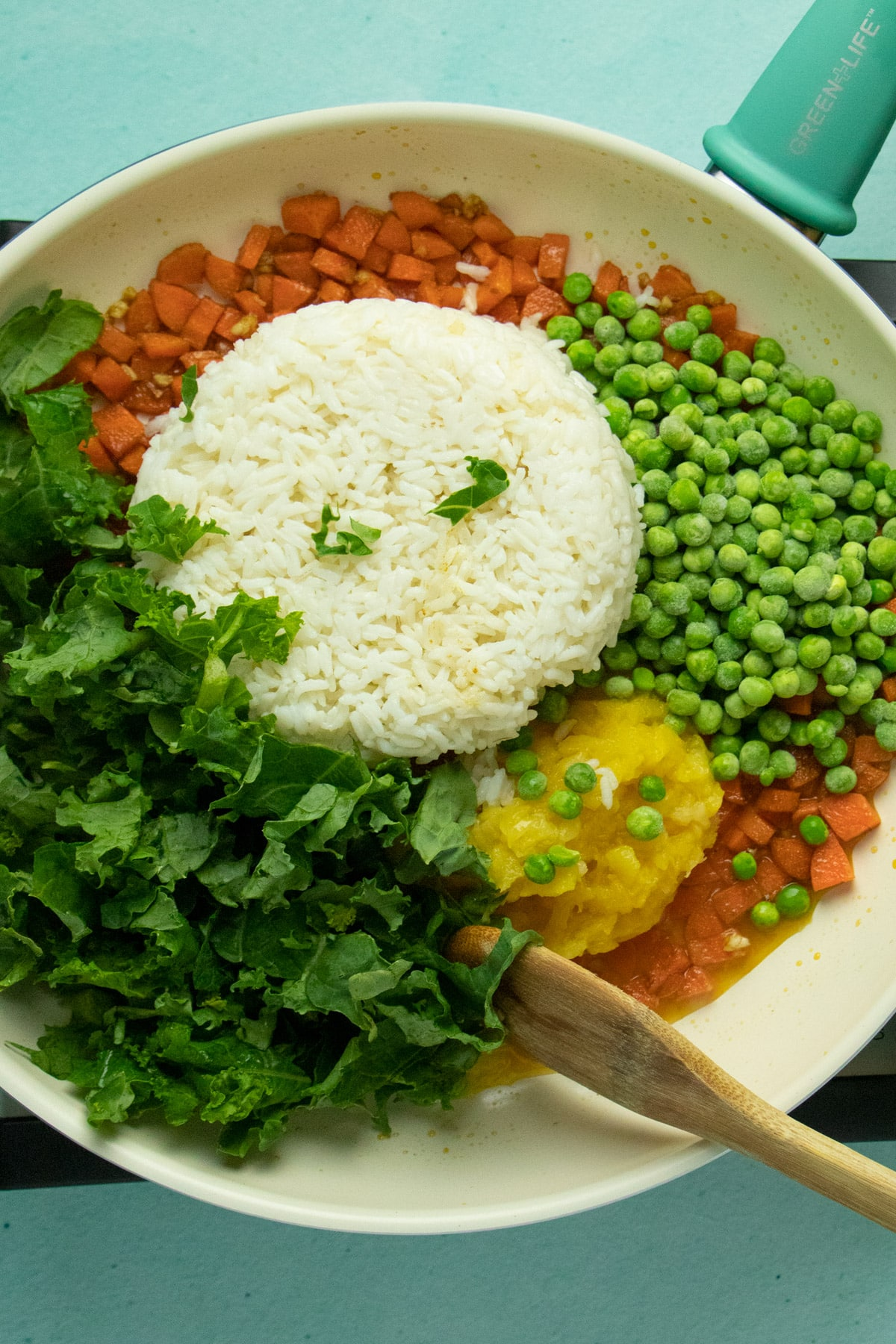 frying pan with rice, peas, kale, pineapple, and carrots