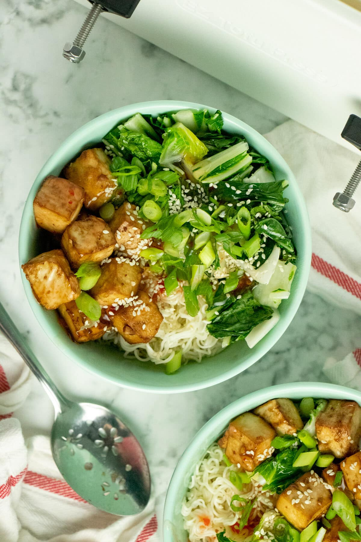 A blue bowl of tofu, noodles, and vegetables