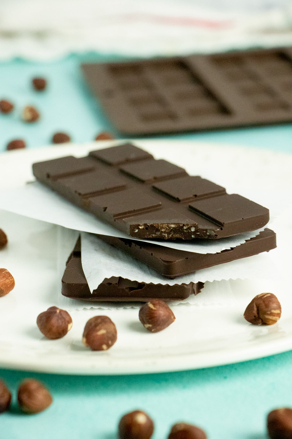 stack of homemade vegan hazelnut chocolate bars on a white plate surrounded by raw hazelnuts. Chocolate bar mold in the background
